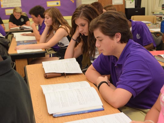 University Academy of Central Louisiana students Kyleigh Dorsey (left) and Christian Cleveland review a school handbook with the rest of their English class Wednesday.
