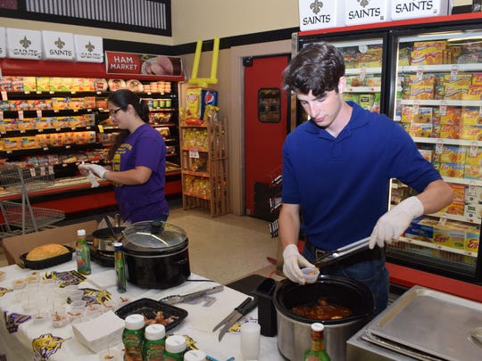 "Mark Powell (right), a Louisiana College junior, and Mary-Jo Brennan (far left) serve food made with Tony Chachere's marinades Saturday at Ball Foods during ""Tailgating with the Cats."" LSU Tiger trivia, in-store demonstrations, giveaways and a cake walk were among activities included in the store's event. A food drive for The Food Bank of Central Louisiana also was held."