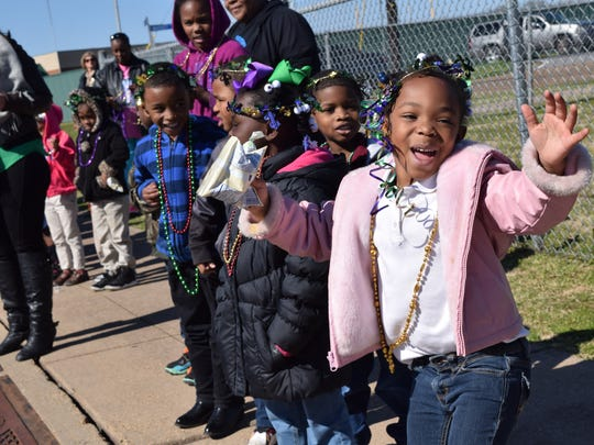 W.O. Hall Elementary Magnet School pre-Kindergarten students wave as the W.O. Hall Mardi Gras parade passes by Thursday afternoon.