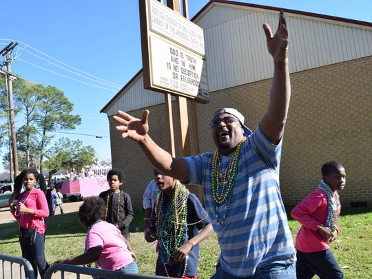 Fritz Von Eric Brantley (front) yells for throws at the 23rd annual krewes parade Sunday. Brantley, who now lives in Houston, brought his children Ja'Kaila Brantley, Bricen Brantley and JaKori Brantley to the parade.
