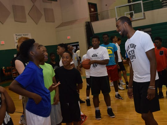 Brooklyn Nets player and former Peabody basketball player Markel Brown (far right) talks with students attending a basketball camp he hosted Friday at Peabody Magnet High School.