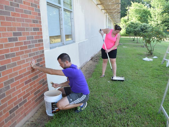 At a work day organized by  Phoenix Magnet Elementary School's Parent Teacher Organization, members paint the outside of the school.