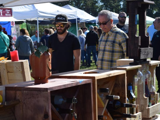 Bryan Adams of Buena shows his custom-made wine racks to Andrew Castellano of Northfield during the Italian Festival at Bellview Winery on Oct. 15.