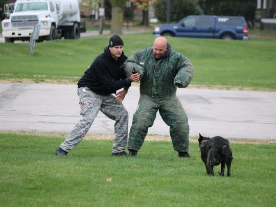 Officer Mark Elliot, of the Marion Police Department, left, and his K9 partner Six perform a pat-down exercise during the evaluator course in Port Clinton.