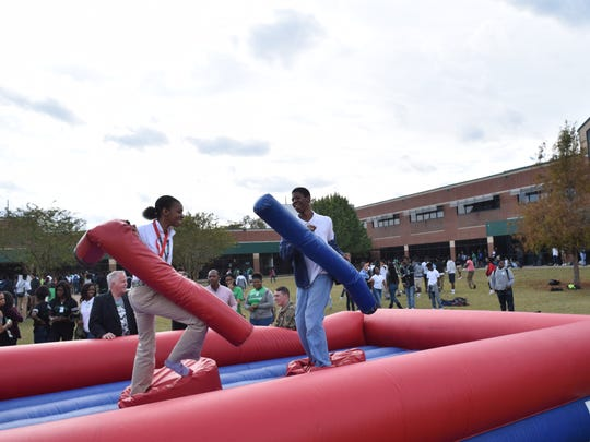 Peabody Magnet High School students Daijah Guerin (left) and Christophe Flournoy joust during a school carnival held at the school the Friday before Thanksgiving.
