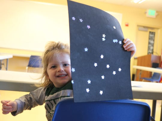 Evie Miller, 3, of Elmore, shows the constellation of stars she made with crafts during 'Nature Tots' at the Ottawa National Wildlife Refuge on Saturday.