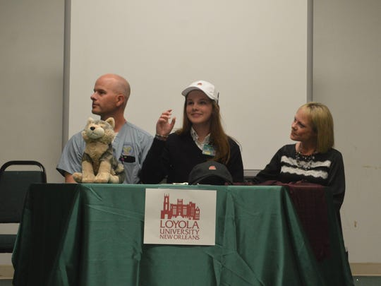 Menard golfer Madison Bates (center) dons a Loyola of New Orleans cap after signing with the Wolf Pack Wednesday.