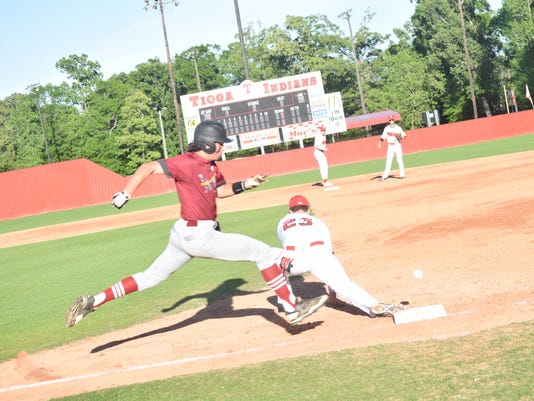 Pineville's Cam Bates (8, left) is safe at first after the ball bounced on the ground as it was thrown Tioga's first baseman Landon Vercher (23, right) in a Tuesday night game.