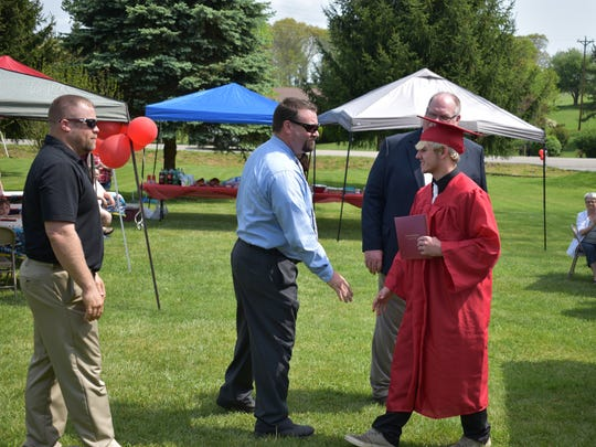 "Riverheads High School senior walks across the ""stage"" at his home on Saturday during an informal ceremony. He shakes hands with principal Max Lowe and assistant principal C.J. Van Devander and wrestling coach Scott Swats."