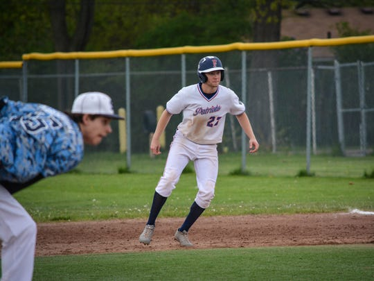 Livonia Franklin's Kyle Wollam eases off first base Saturday while Livonia Stevenson reliever Josh Marquedant delivers a pitch to the plate.