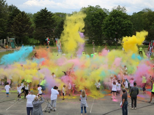 At the end of the race, Edgerton Elementary students used color packs they had earned through fundraising to create a cloud of color.
