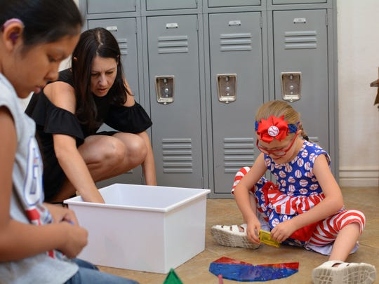 Jessika Reed plays with magnetic building blocks with daughters Cassara (left) and Parys.