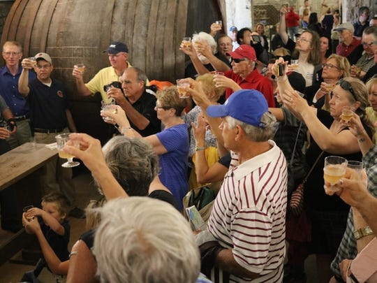Both state and local officials, along with many members of the public, toast to the reopening of the historic Lonz Winery building from within its famous cellars on Middle Bass Island.