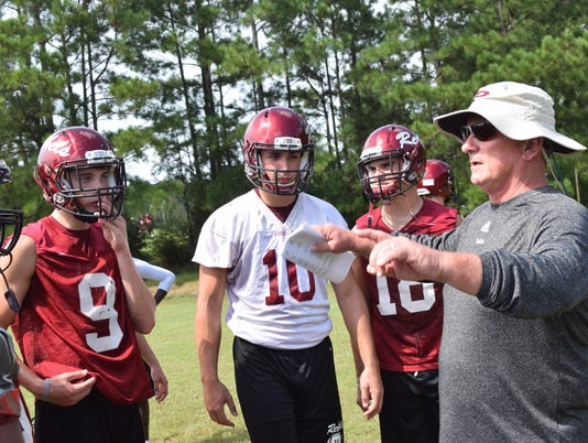 Pineville head football coach Dennis Dunn coaches players at practice.