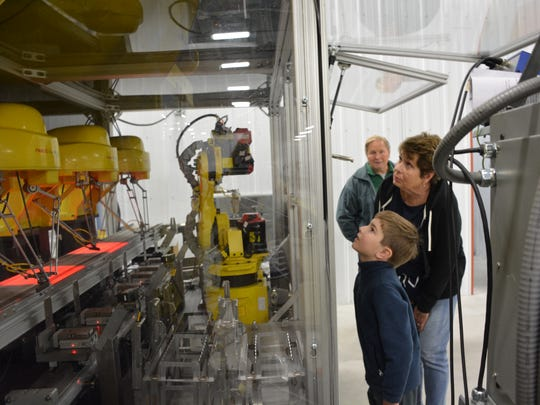 Henri Jeanquart, 8, studies a series of automated laser tools at Cadence, Inc., Sturgeon Bay, while his grandparents, Joan and Dale Jeanquart, watch during a tour of the industry Saturday, Oct. 21, 2017.