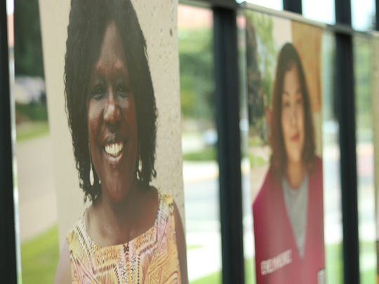 A photo shows the banners that are part of a local version of Green Card Voices exhibit on display in Aberdeen, South Dakota. Each banner features a first-generation immigrant or refugee, with a link to YouTube videos of each telling their story.
