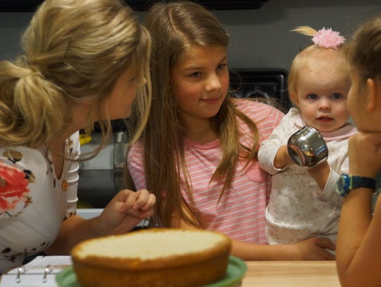 Erin Bates Paine, left, makes a cake with family.