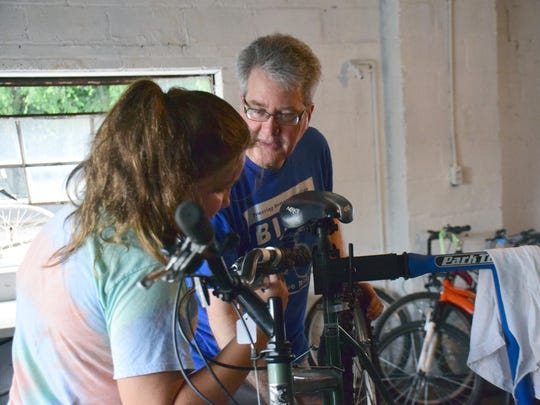 Volunteer Randall Wolf works with Brookelyn Meadows on a bike during a summer workshop at the Bike Box of the Blue Ridge on Tuesday, July 17, 2018, at the Boys & Girls Club of Waynesboro, Staunton and Augusta County in Waynesboro, Va.