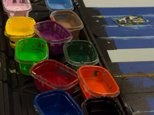 Small tubs of paint line table inside an art room at Millsboro Middle School, waiting to be used in the school's ongoing mural project.