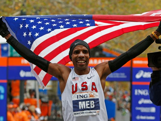 In this Nov. 1, 2009, file photo, Meb Keflezighi holds