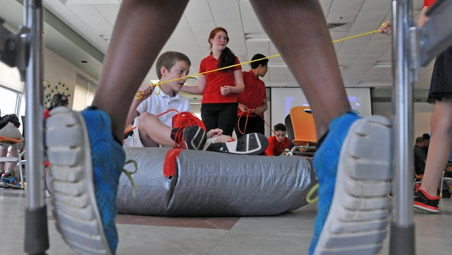 The 7th grade students of Veteran Memorial School build their own hovercraft during the AMSA Hovercraft Trials on Tuesday. Ronald Sauerbrey (driver) along with Alyssa Webb (center), Fiaviana Cohen(right) and others help build the craft. June 16, 2015.