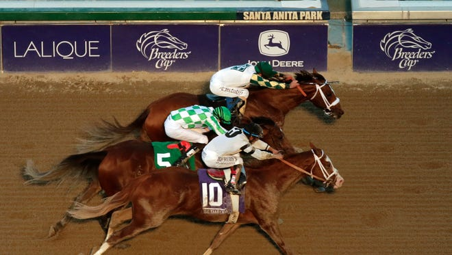 Jockey Gary Stevens, top, rides Mucho Macho Man to victory in the Breeders' Cup Classic horse race ahead of Will Take Charge, bottom, and Declaration of War at Santa Anita Park on Nov. 2.