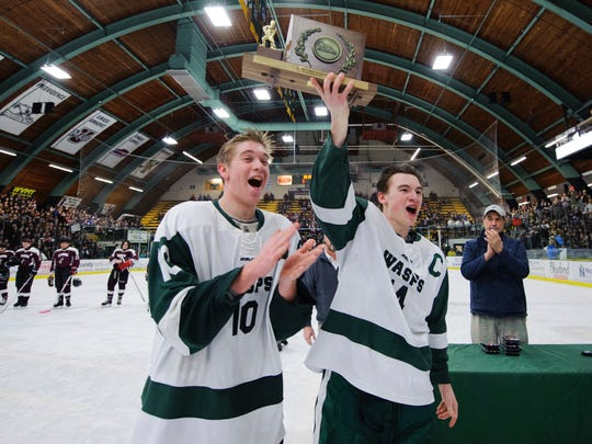 Woodstock's Steven Townley (10) and Woodstock's Cullen McCarthy (14) hold up the championship trophy during the Vermont state division II boys hockey championship game between Lyndon and Woodstock at Gutterson Field House on Monday evening March 19, 2018 in Burlington.