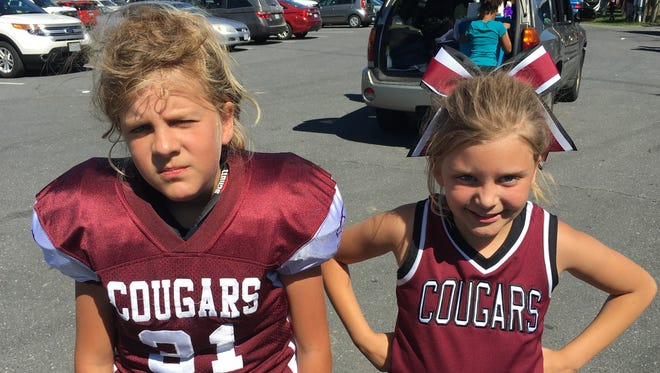 Mackenzie, left, and Madison Conner are 10-year-old fraternal twins. Mackenzie plays football for the Stuarts Draft Quarterback Club, while Madison cheers for the team.