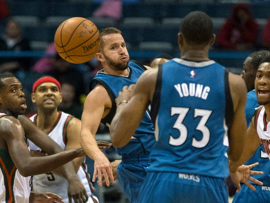 Milwaukee Bucks' Khris Middleton, left, watches the ball as Minnesota Timberwolves' J.J. Barea, center, passes back to teammate Thaddeus Young (33) during the first half of an NBA basketball game Wednesday, Oct. 22, 2014, in Milwaukee. (AP Photo/Tom Lynn)