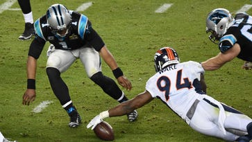 Broncos outside linebacker DeMarcus Ware grabs a fumble ahead of Panthers quarterback Cam Newton during the fourth quarter.