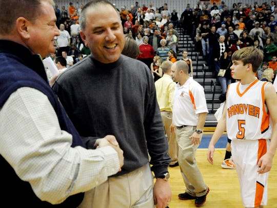In this file photo from February 2011, Dallastown athletic director Tory Harvey congratulates Central York boys' basketball head coach Marty Hasenfuss on his 300th career victory.