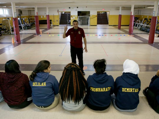 Students at the Rochester Academy Charter School listen to teacher Rich Vleck as he gives instructions in a makeshift gym in the basement of the school's Portland Avenue campus.
