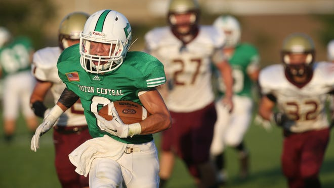 Triton Central wide receiver Brady Gossett runs down the field with Lutheran High School Saints players in pursuit on his 64-yard first quarter touchdown on the Tiger's home field in Fairland on Friday, September 5, 2014.