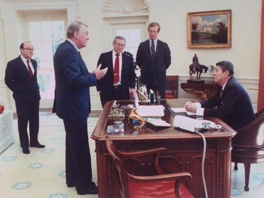 Pres. Reagan (R) sitting at his Oval Office desk, looking up at earnestly speaking Ed Meese, mtg. w. Atty. Gen. & (standing behind) Chief of Staff Howard Baker (C) & his aide Arthur Culvahouse (R).