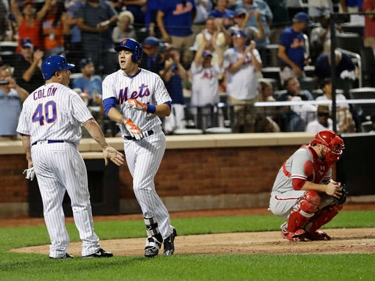 New York Mets' Wilmer Flores, center, celebrates with Bartolo Colon, left, as Philadelphia Phillies catcher Cameron Rupp, right, reacts after Flores hit a grand slam during the fifth inning of a baseball game Friday, Aug. 26, 2016, in New York. (AP Photo/Frank Franklin II)