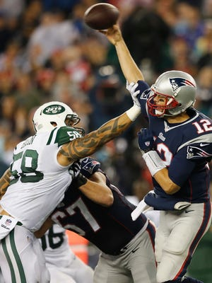 FOXBORO, MA - OCTOBER 16:  Jason Babin #58 of the New York Jets tackles Tom Brady #12 of the New England Patriots during the second quarter at Gillette Stadium on October 16, 2014 in Foxboro, Massachusetts.  (Photo by Jim Rogash/Getty Images)