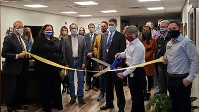 The Ambassador Committee of the Macomb Area Chamber of Commerce cuts the ribbon for the Downtown Residential Development Corporation (DRDC) upon the completion of a new private residence above MidAmerica National Bank, located at 130 N. Side Square.