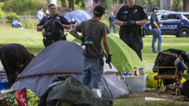 Eugene police stand by as campers pack their belongings after the City of Eugene served eviction notices to people who have been calling Washington Jefferson Park home during the COVID-19 pandemic. [Chris Pietsch/The Register-Guard] - register-guard.com