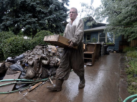 Robert Frawley, of Burggraf Disaster Restoration, carries destroyed belongings out of a flooded home on Iris Avenue on Sept. 15, 2013, Boulder, Colo.