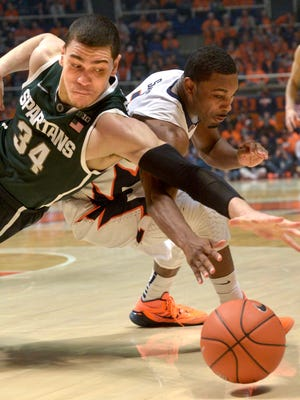 Michigan State forward Gavin Schilling and Illinois' Ahmad Starks go after a loose ball Sunday night in Champaign.