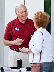 Poll Worker Joel Sears talks to voter Carolyn Hall,