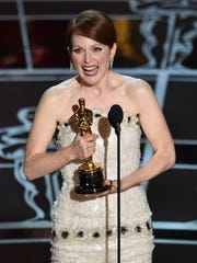 "Julianne Moore accepts the award for best actress in a leading role for ""Still Alice"" at the Oscars on Sunday, Feb. 22, 2015, at the Dolby Theatre in Los Angeles. (Photo by John Shearer/Invision/AP)"