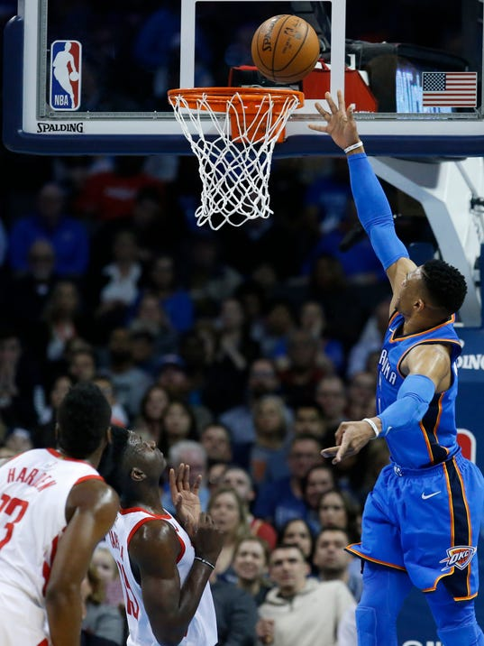 Oklahoma City Thunder guard Russell Westbrook, right, shoots in front of Houston Rockets guard James Harden (13) and center Clint Capela, center, in the first half of an NBA basketball game in Oklahoma City, Tuesday, March 6, 2018. (AP Photo/Sue Ogrocki)