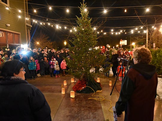 People gather around a large Christmas tree for a lighting