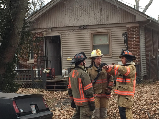 Evansville firefighters discuss the situation at the scene of a house fire in the 800 block of Taylor Avenue that killed one person Sunday afternoon.