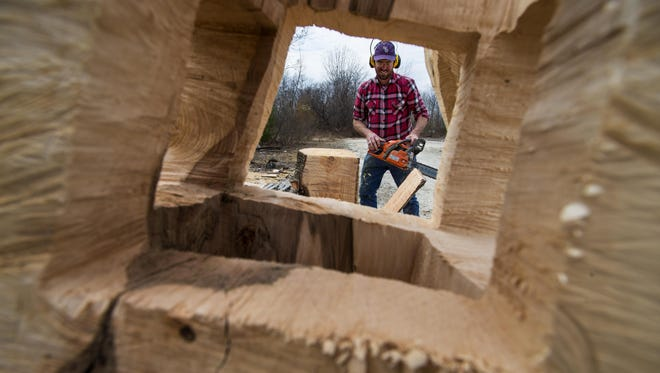 Clark Derbes is framed by one of his works as he uses a chainsaw to shape a pine log outside his studio in Burlington on Monday, April 18, 2016.