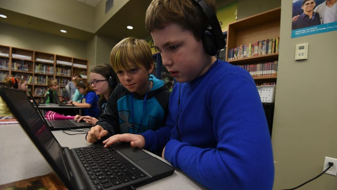 Fourth-grader Evan Beck (middle) helps Landon Witt with coding Thursday at Hackler Intermediate. The school library has a maker space that allows students to do more than checking out books.