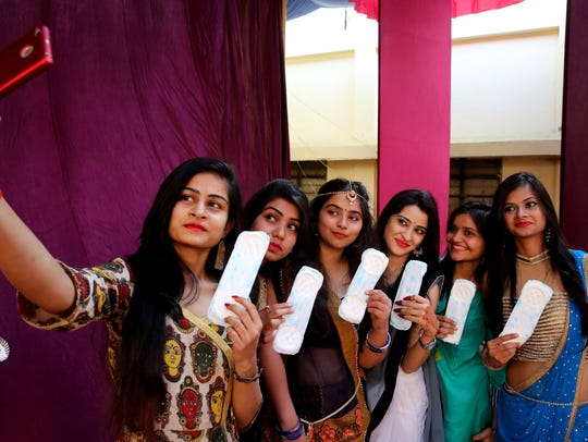 Indian college students take photographs holding sanitary pads to create awareness in Government Sarojini Naidu Girls College in Bhopal, India.
