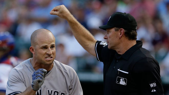 The Yankees' Brett Gardner, left, yells at home plate umpire Ed Hickox  after a strike three call against Gardner during the second inning of Wednesday night's game against the Texas Rangers in Arlington, Texas.