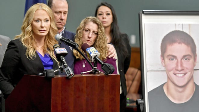 FILE – In this May 5, 2017, file photo, Centre County, Pa., District Attorney Stacy Parks Miller, left, announces findings an investigation into the death of Penn State University fraternity pledge Tim Piazza, seen in photo at right, as his parents, Jim and Evelyn Piazza, second and third from left, stand nearby during a news conference in Bellefonte, Pa. Parks Miller reinstated certain charges against members of Penn State's former Beta Theta Pi fraternity Friday, Oct. 27, 2017, nearly two months after a district judge dismissed the most serious charges of involuntary manslaughter and aggravated assault originally filed by prosecutors in response to the Feb. 4, 2017, death of 19-year-old Tim Piazza, of Lebanon, N.J., after a night of heavy drinking. (Abby Drey/Centre Daily Times via AP, File)